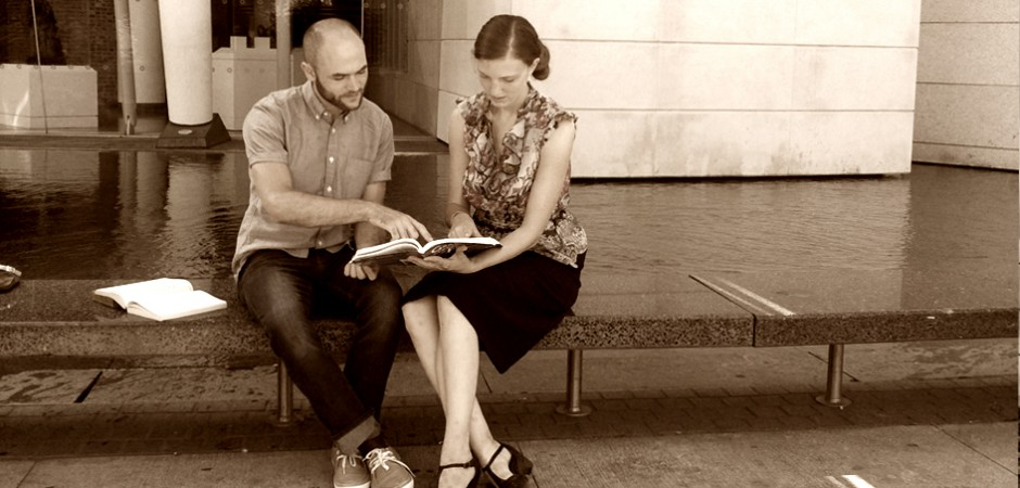 Young man patiently teaching a young woman French during a lesson in a serene modern setting