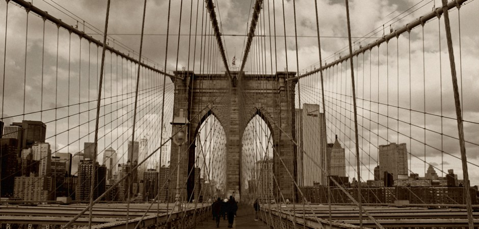 a wide-angle shot of the Brooklyn Bridge, empty and calm on a cloudy day, in a vintage sepia tone