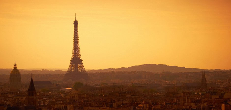 A romantic, golden and hazy Paris panoramic view at sunset featuring the Eiffel Tower and the Sacré Coeur.